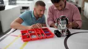 Equipo de ingenieros jovenes que trabajan en la máquina robótica