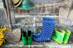 Equipo de jardín - botas de goma, schovels y sombreros del srtaw en sunn imágenes de archivo libres de regalías