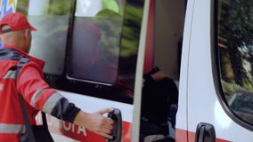 Equipo de la ambulancia que deja el transporte, paramédicos que caminan al paciente, ayuda urgente metrajes