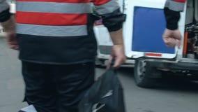 Equipo de la ambulancia que se apresura y que consigue en el coche de la emergencia, listo para ahorrar vidas almacen de metraje de vídeo