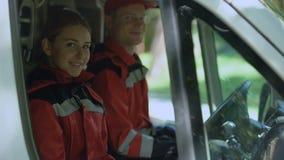 Equipo de la ambulancia que se sienta en el transporte, servicios médicos de la emergencia profesional almacen de metraje de vídeo