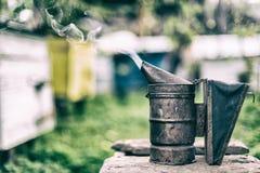 Equipo de la apicultura - fumador de la abeja, proceso de obtener la miel, poseer seguridad Imagen de archivo