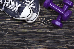 Equipo de la aptitud y de deporte: zapatillas de deporte, pesas de gimnasia en fondo de madera Fotografía de archivo