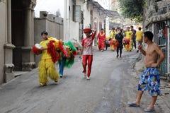 Equipo de la danza de león que camina en el callejón Imagenes de archivo
