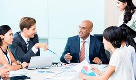 Equipo de la diversidad en la reunión del desarrollo de negocios con las cartas