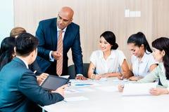 Equipo de la diversidad en la reunión del desarrollo de negocios con las cartas Foto de archivo libre de regalías