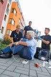 Equipo de la emergencia que ayuda al paciente herido en la calle Foto de archivo libre de regalías