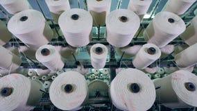Equipo de la fábrica de la materia textil Los hilos blancos están enrollando entre los carretes almacen de video