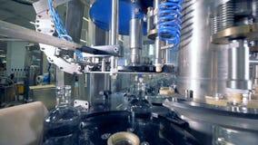 Equipo de la fábrica que coloca los casquillos en las botellas, cierre para arriba Equipo industrial automatizado almacen de metraje de vídeo