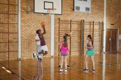 Equipo de la High School secundaria que juega a baloncesto Imágenes de archivo libres de regalías