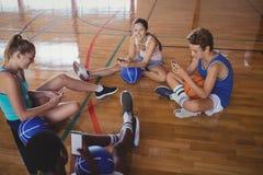 Equipo de la High School secundaria usando el teléfono móvil mientras que se relaja en la cancha de básquet Fotografía de archivo libre de regalías