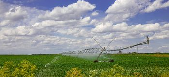 Equipo de la irrigación en campo de granja con las nubes blancas Fotografía de archivo libre de regalías