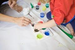 Equipo de la mujer y del niño que trabaja preparando pinturas Imagen de archivo libre de regalías