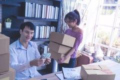 Equipo de la pequeña empresa que comprueba la acción en su negocio casero en línea foto de archivo libre de regalías
