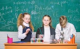 Equipo de la qu?mica estudiantes que hacen experimentos de la biolog?a con el microscopio en laboratorio Ni?os que aprenden qu?mi imágenes de archivo libres de regalías