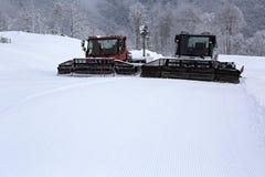 Equipo de la retirada de la nieve de la paleta en las montañas de Imagen de archivo