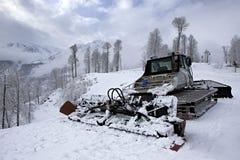 Equipo de la retirada de la nieve de la paleta en las montañas de Imagenes de archivo