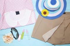 Equipo de la ropa y de accesorios de la mujer en backgroun de madera azul Foto de archivo libre de regalías