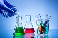 Equipo de laboratorio, botellas, frascos con el líquido del color, mano vertida imágenes de archivo libres de regalías