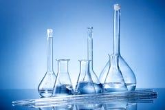 Equipo de laboratorio, frascos de cristal, pipetas en fondo azul Foto de archivo libre de regalías