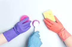 Equipo de limpieza que lleva guantes protectores y que lleva a cabo diversos artículos de limpieza para hacer para limpiar su cas imagen de archivo libre de regalías