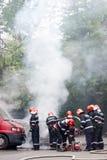 Equipo de los bomberos que extingue un coche en el fuego fotos de archivo libres de regalías