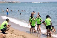 Equipo de los deportes de los niños con los entrenadores en la playa de Barceloneta Fotos de archivo libres de regalías