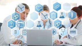 Equipo de los doctores que discute sobre diversos iconos del ordenador portátil