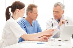 Equipo de los médicos usando el ordenador. El ir del equipo de los médicos Imagen de archivo libre de regalías