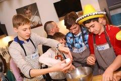 Equipo de los niños del adolescente que cocina divirtiéndose Imagen de archivo