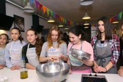 Equipo de los niños del adolescente que cocina divirtiéndose Imagen de archivo libre de regalías