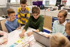 Equipo de los niños, del ordenador portátil y de la invención en la escuela de la robótica foto de archivo