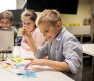 Equipo de los niños, del ordenador portátil y de la invención en la escuela de la robótica imagen de archivo