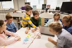 Equipo de los niños, del ordenador portátil y de la invención en la escuela de la robótica foto de archivo libre de regalías