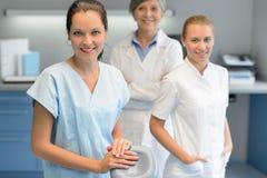 Equipo de mujer de tres dentistas en la cirugía dental fotos de archivo