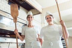 Equipo de mujeres del panadero que se colocan en la panadería que da los pulgares para arriba imagenes de archivo