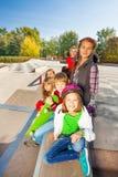Equipo de niños con los monopatines y los cascos Foto de archivo