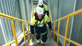 Equipo de obreros de sexo masculino que llevan el uniforme protector que sube en las escaleras almacen de metraje de vídeo