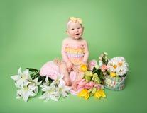 Equipo de Pascua del bebé, con los huevos y las flores Foto de archivo