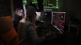 Equipo de piratas informáticos, cortando los ordenadores, trabajando en sitio oscuro metrajes