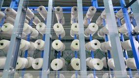 Equipo de producción de la fábrica de la ropa Los hilos blancos están formando la tela mientras que desenrollan almacen de video