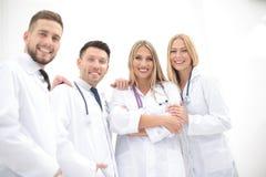 Equipo de profesionales médicos que miran la cámara, sonriendo Foto de archivo libre de regalías