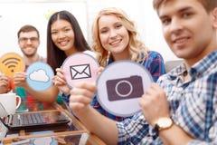 Equipo de promotores jovenes que se sientan en la tabla Imágenes de archivo libres de regalías