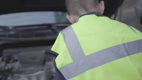 Equipo de seguridad del pequeño muchacho que lleva confiado que hace una pausa la capilla abierta de un coche quebrado Muchacho q almacen de video