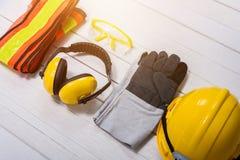 Equipo de seguridad estándar de construcción en la tabla de madera foto de archivo