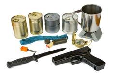 Equipo de supervivencia con los suministros de emergencia y el arma Fotografía de archivo libre de regalías