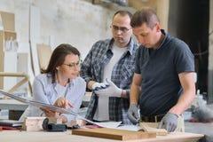 Equipo de trabajadores del taller de los carpinteros que discuten un proyecto de los muebles con el cliente, diseñador, ingeniero imagen de archivo