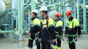 Equipo de trabajadores profesionales en ropa y casco protectores que caminan en sitio de la instalación de producción almacen de video