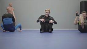Equipo de tres personas: hombres y mujer que hacen gastos indirectos rodantes en el piso en el gimnasio almacen de video