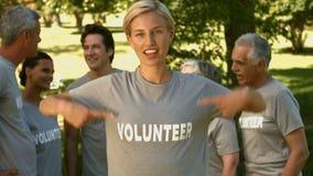 Equipo de voluntarios felices en el parque metrajes
